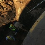 Another construction worker makes his way down in the hole by the stream that runs underneath the streets of Ishpeming