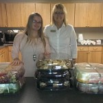 LeAnne Kachmarsky (right) standing in front of the delicious food donated by Super One Foods of Marquette