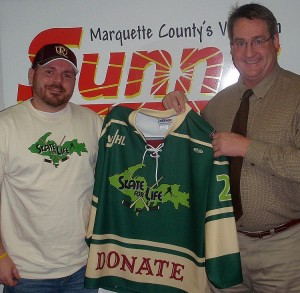 Marquette Royales Asst. Head Coach Cliff Cook and GLR Sales Exec Jim Parks with on of the team jersey up for auction.