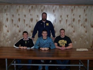 Head Coach Paul Jacobson stands behind (From Left to Right) Tyler LaJoie, Zane Radloff, and Jeremy Bell as they sign their letter of intents.