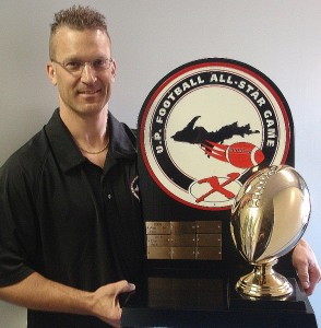 Todd Goldbeck, organizer of the U.P. Football All-Star Game with the game trophy.