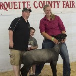 Shelby and her sheep with the buyer and his son at the Marquette County Fair 4-H Livestock Auction 2015