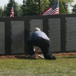 Man Kneels Down to Pay Respects