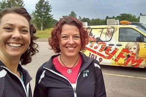 Glory Sparx and Phee Nix from the Dead River Derby admiring the vintage SUNNY FM van.