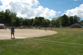 Softball Very Popular with Crowd and Kids on a Beautiful Summer Day