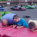 Family participating in a watermelon eating contest.