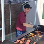Econo Foods Employee grills up lunch for community members.