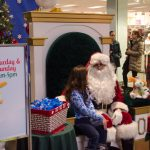 Telling Santa what she wants for Christmas.