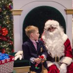 Nicely dressed young man meeting Santa.