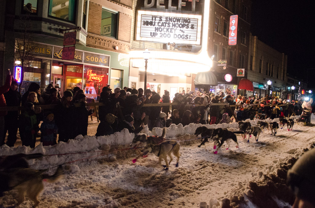 The crowd ran cow bells as the dogs ran by.