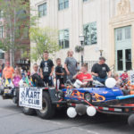 All of the kids from the Marquette Kart Club where sitting in their karts on the float.