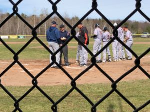 Team leaders meet at home plate before the Negaunee home baseball opening game