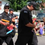 Police officers throw freeze pops to kids during the Pioneer Festival Parade