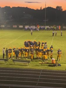 The Miners huddle up on the sideline in their 30-6 to the Calumet Copper Kings on Sunny 101.9FM.
