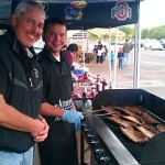 Tadych's Econo Foods General manager Zack Quinnell (right), standing next to Bill Tibor (left) of Great Lakes Radio,  is tending to a brand new item, Ktetschmar baby back Pork ribs.
