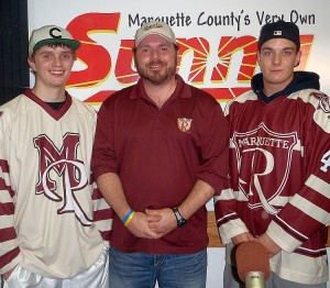 Marquette Royales players Tanner Doty and Jesper Tiselius in the new uniforms flank Asst. Coach Cliff Cook.