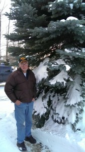 Marquette Township resident, Ken Ceckiewicz, with the 30' Blue Spruce tree he donated to the township.