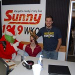 The Grinch, Max, and Carl in front of Sunny 101.9 Poster