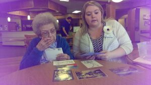 Sarah DeRoche Memory Care Activities Director working with a resident