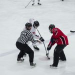 Another face off during the Pigs-N-Heat charity hockey game.