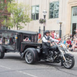 A beautiful hearse pulled by a tricycle