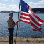 A Boy Scout holding the flag next to the Lower Harbor