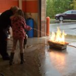 This little girl is having fun putting out a real fire