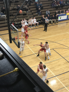 Both teams look on at a Negaunee three-point attempt, as the Miners defeated the Patriots 49-46 on 101.9 SunnyFM.