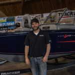 Dane next to one of the boats at the Allstar Marine set up