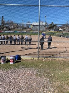 Both teams stand prior to the game for the national anthem.