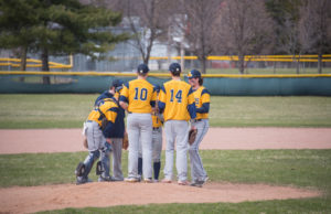 The Negaunee Miners take a break on the pitchers mound to regroup.