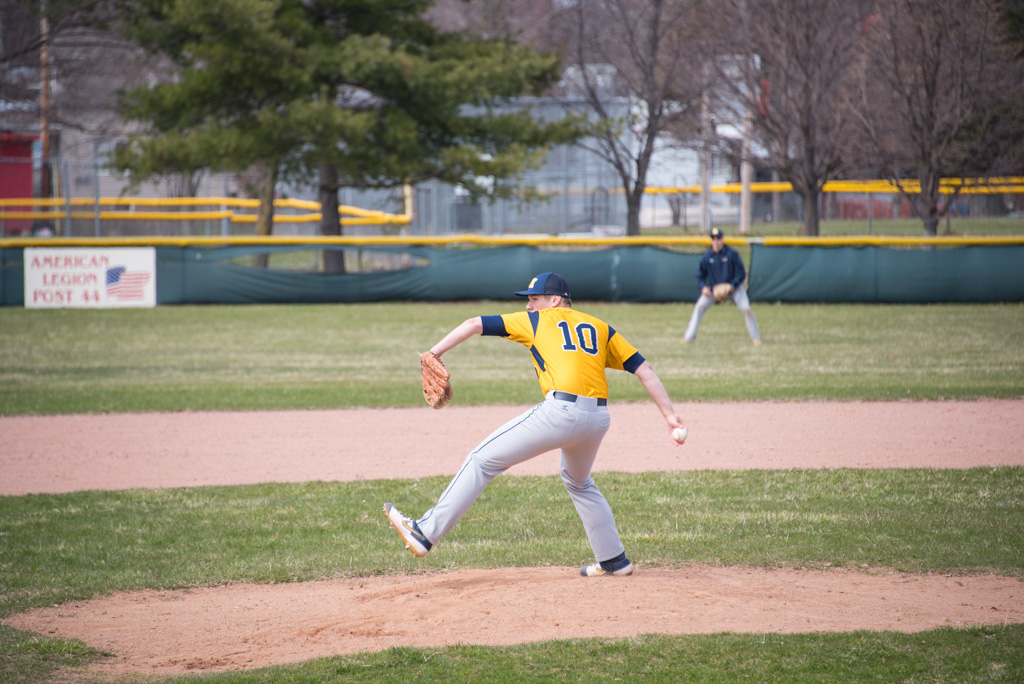 The Negaunee Miners baseball team pitcher throwing one at the Redmen batter on home plate.