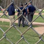 The umpires talk with the coaches before the game gets underway