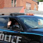 Ishpeming police wave to crowd at Pioneer Day parade