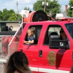 Waving to crowd in Ishpeming Fire Department truck during 2019 Pioneer Days Parade