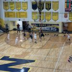 The Negaunee Miners attack the basket.