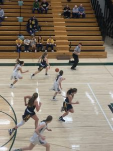 The Miners run up the floor on the fast break in its 59-21 win over Manistique on Sunny 101.9.