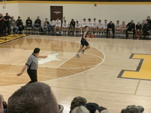 Jakson Sager brings the ball across halfcourt for the Miners.