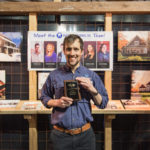 """Ben holding the """"Best Double Booth"""" award for Michael's Homes"""