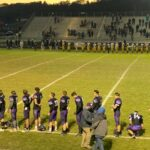 Both teams line up for the national anthem prior to Friday's playoff game.