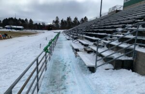 Snow covered the bleachers and field before Saturday's game.