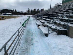 Snow covered the bleachers and field at Miners Stadium.