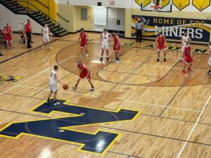 Negaunee's Mason Sager dribbles up the court for the Miners while being guarded by his cousin, Marquette's Lincoln Sager.