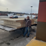 Paul next to the trailer with wood for the shed.