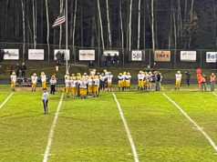 The Miners huddle up on their sideline during Friday's night game against Westwood.